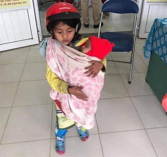 Nghẹn ngào hình ảnh chị 7 tuổi địu em 5 tháng tuổi đi tiêm chủng